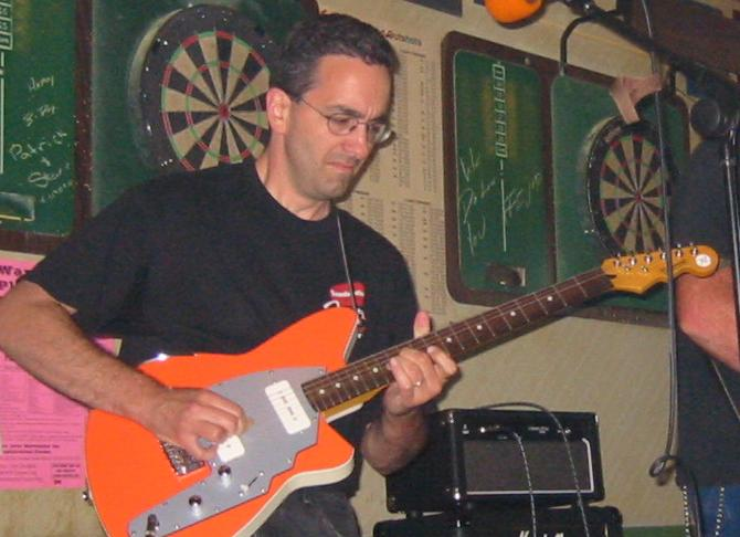 Dan Skidmore professional guitarist playing electric guitar in a show.