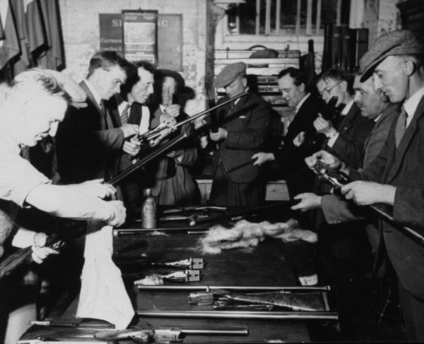 Vintage men cleaning the guns rifles.