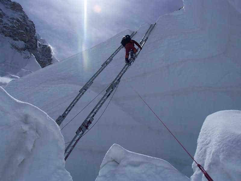 A man climbing on snow mountain with the help of leader.