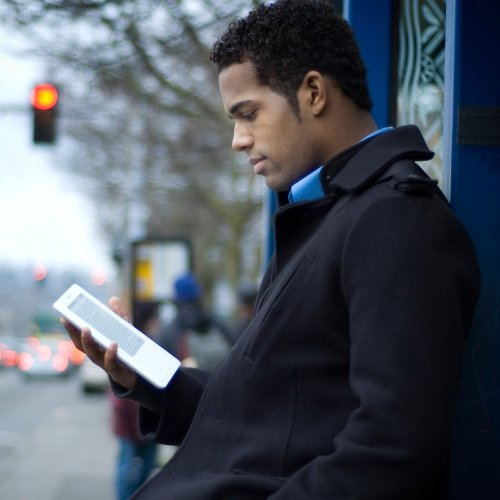 young african american man reading amazon kindle
