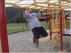 man doing pull up on swingset playground workout