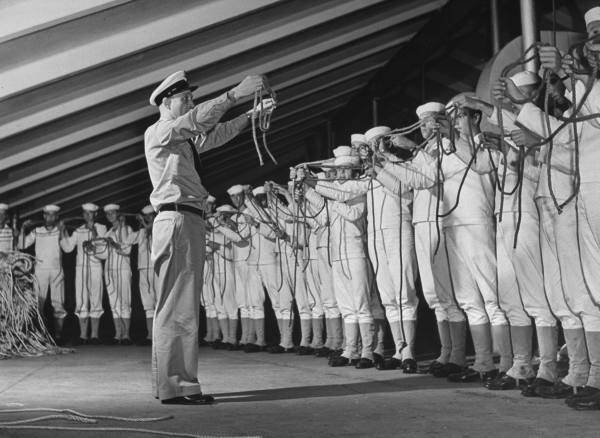 Vintage instructor teaching sailors how to tie knots.