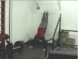 Man Legs on wall doing push ups in a gym.