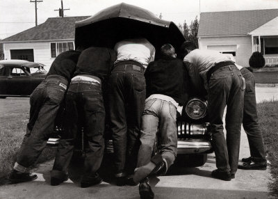 vintage group men working on car under hood