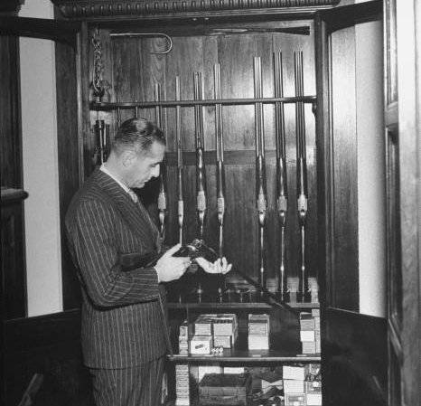 vintage gun rack man inspecting weapons