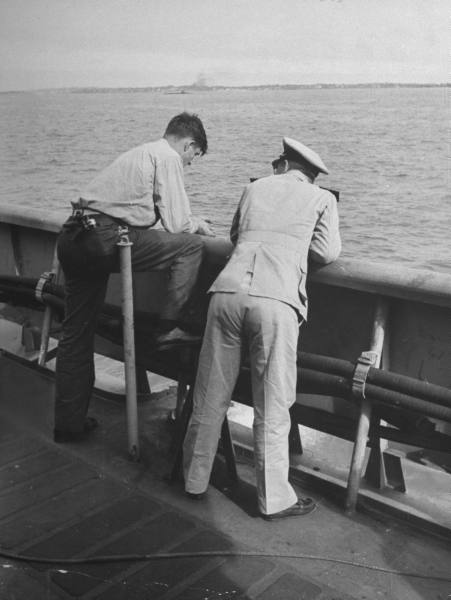 vintage sailors standing at railing near water