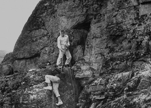 vintage men mountain climbing cliff face