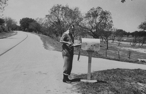 Vintage man getting mail from mailbox beside the road.