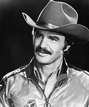 Burt Reynolds wearing cowboy hat showing mustache.