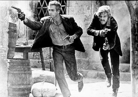 Butch Cassidy and the Sundance kid running in the street and holding guns in both hands.