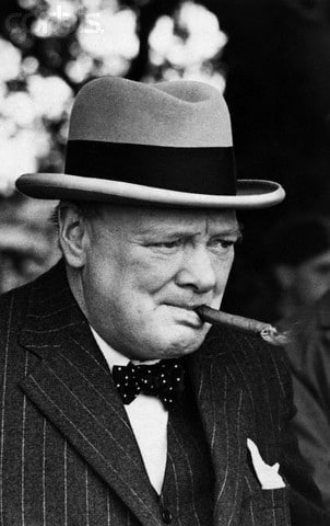 Winston Churchill with a hat smoking a cigar.