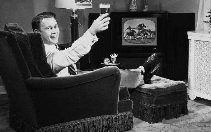 Formal man lying on chairand cheering beer while watching tv.