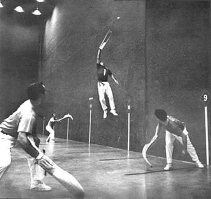 Vintage jai alai player jumping in air while playing.