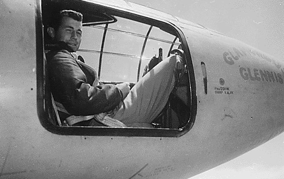 Chuck Yeager sitting in the nose of airplane.