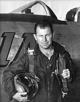 Vintage Chuck Yeager standing in front of airplane.