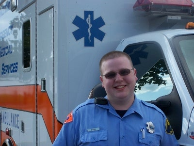nate dionne emt uniform in front of ambulance