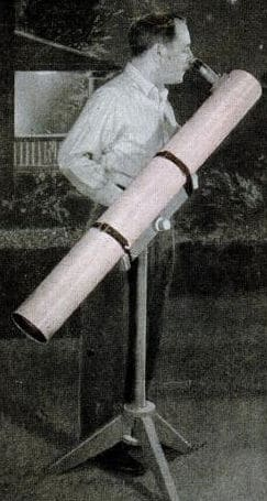 Vintage man looking through large backyard telescope.