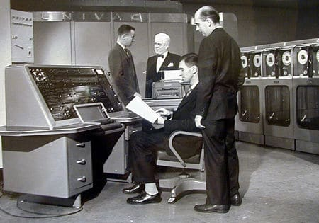 Vintage 1950s computers men in room programming.
