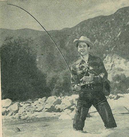 Vintage man fishing in river near mountains.