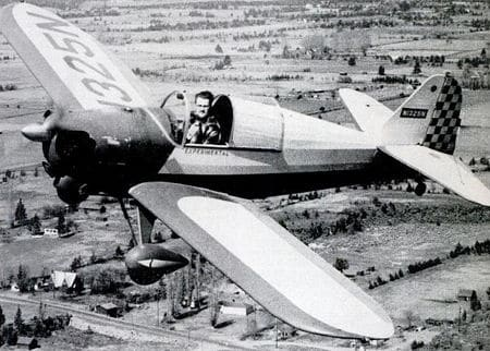 Vintage pilot in open-air cockpit aerial shot.