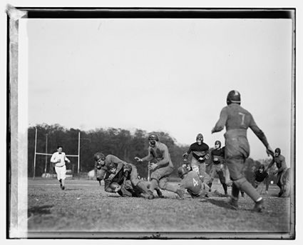 Vintage football players wearing helmets during game.