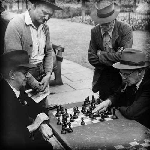vintage old men playing chess in park