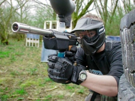 Man playing paintball modern gun helmet equipment.