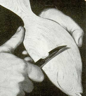 Man whittling fish out of wood with pocket knife.