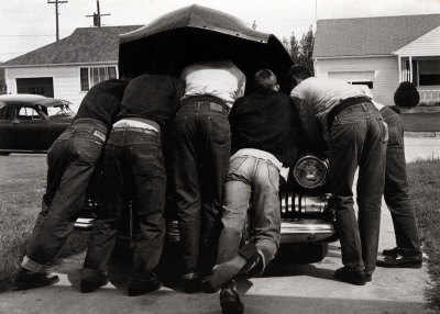 Vintage men working on car hood up.