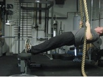 Man doing exercise of rope holding at gym.