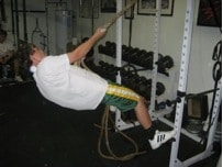 Man doing exercise of rope climbing at gym.