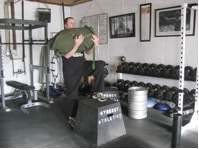 Man doing exercise of front hold sandbag at gym.
