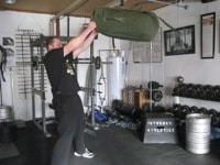 Man doing exercise of sandbag pulling at gym.
