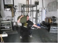 Man doing exercise of shoulder sandbag at gym.