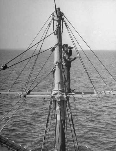 man in crow's nest ship lookout with binoculars