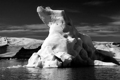 iceberg in water black white ocean sea ice