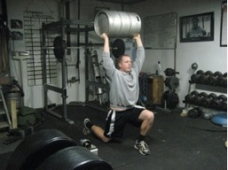 Man doing exercise of keg holding at gym.