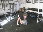 Man doing exercise of keg sit ups at gym.