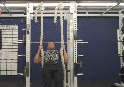 A man doing supine rows heavy ropes training in gym.