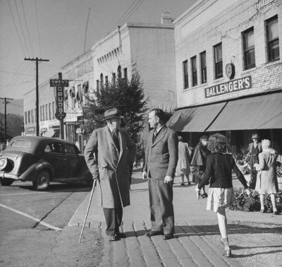 vintage men walking and talking on sidewalk downtown