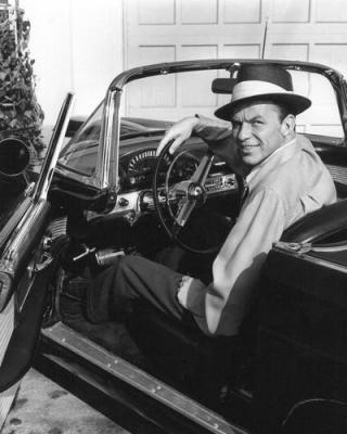 Frank sinatra in convertible wearing hat.