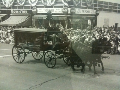 Funeral carried on horses along with several people watching it.