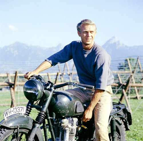 A man on a motor bike fences and mountains in background.