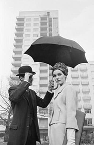 mid 20th century vintage man holding umbrella for woman