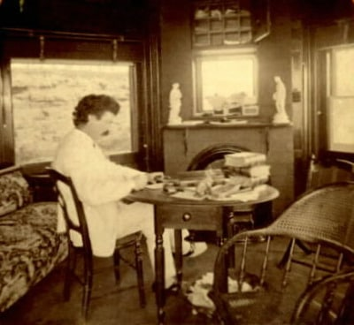 Mark twain busy in writing at table in the hut.