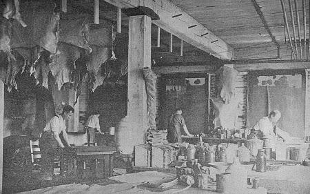 Vintage men working in leather workshop.