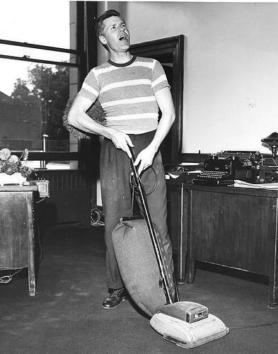 vintage man vacuuming floor cleaning