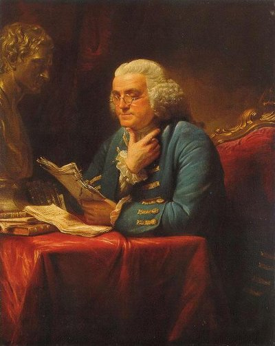 Benjamin Franklin sitting at table and reading papers portrait.