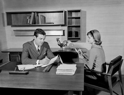 vintage boss and secretary at desk taking notes