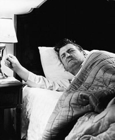 Vintage man waking up in grumpy mood and turning on the lamp.